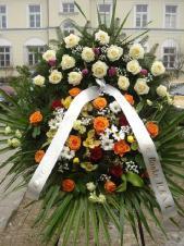 Wieniec z żywych kwiatów, wielkość: średni, róża kremowa (Avalanche), róża herbaciana, tulipan fioletowy, goździk bordowy, storczyk zielony, storczyk złoty, goździk gałązkowy kremowy, zieleń dekoracyjna, liść palmy, podkład jodłowy, szarfa taśma PP szer. 8 cm druk cyfrowy.