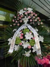 Wieniec pogrzebowy z kwiatów żywych, wielkość: duży, lilie białe (Casablanca), róże różowe (Dolce Vita), anthurium zielone (Midori), liść palmy, podkład jodłowy, zieleń dekoracyjna, szarfa satynowa 10cm, druk komputerowy.