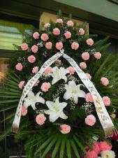 Wieniec pogrzebowy z żywych kwiatów, wielkość: średni, goździki różowe, lilie białe, liście palmy, podkład jodłowy, zieleń dekoracyjna, szarfa satynowa 7cm, druk komputerowy (+20zł).