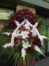 Wieniec pogrzebowy z żywych kwiatów, wielkość: bardzo duży, róże pąsowe, lilie białe (Simplon), mieczyk biały, liść palmy, podkład jodłowy, zieleń dekoracyjna, szarfa satynowa 7cm, druk komputerowy (+20zł).