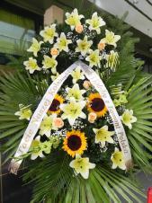 Wieniec pogrzebowy z żywych kwiatów, wielkość: duży, lilie kremowe (Conca D'or), róże kremowe (Kiwi), słoneczniki, liść palmy, cykas, podkład jodłowy, zieleń dekoracyjna, szarfa satynowa 7cm, druk komputerowy.