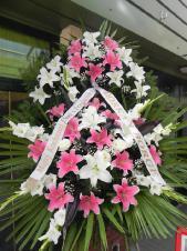 Wieniec pogrzebowy z żywych kwiatów, wielkość: duży, lilie różowe (Sorbona), lilie białe (Rialto), mieczyk biały, liść palmy, podkład jodłowy, zieleń dekoracyjna, szarfa satynowa 7cm, druk komputerowy.