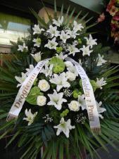 Wieniec pogrzebowy z kwiatów żywych, wielkość: duży, lilie białe (Casablanca), anthurium zielone (Midori), róże kremowe (Avalnanche), chryzantema zielona (Santini), liść palmy, podkład jodłowy, zieleń dekoracyjna, szarfa satynowa 7cm, druk komputerowy.