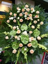 Wieniec z kwiatów żywych, wielkość: duży (ok. 1,4 m), mieczyk zielony, anthurium zielone (Midori), róża herbaciana (Peach avalanche), eustoma biała, podkład jodłowy, zieleń dekoracyjna.