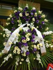 Wieniec z żywych kwiatów, wielkość: duży (ok. 1,6 m), mieczyk biały, eustoma fioletowa, eustoma kremowa, lilia biała, cantadeskia żółta, , liść palmy, podkład jodłowy, zieleń dekoracyjna.