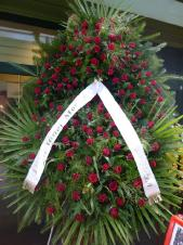 Wieniec z żywych kwiatów, wielkość: bardzo duży (ok. 1,8 m); róża czerwona (Red Ribbon), liść palmy, podkład jodłowy, zieleń dekoracyjna.
