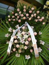 Wieniec z żywych kwiatów, wielkość: duży, storczyki białe (Cymbidium), róże różowe, lilie białe, liść palmy, podkład jodłowy, zieleń dekoracyjna, szarfa satynowa biała 7cm. szer.(20zł).