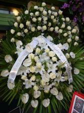 Wieniec z żywych kwiatów, wielkość: bardzo duży, anthurium białe, róża kremowa (White Naomi), lilia biała, liść palmy, zieleń dekoracyjna, podkład jodłowy, szarfa satynowa o szer. 10 cm (+30 zł).