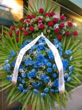 Wieniec z żywych kwiatów, wielkość: bardzo duży, róże pąsowe, chryzantemy gałązkowe niebieskie, liść palmy, podkład jodłowy, szarfa satynowa czarna, druk komputerowy (+20zł).