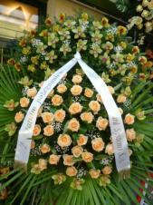 Wieniec z żywych kwiatów, wielkość: bardzo duży, storczyki zielone (Cymbidium), róże łososiowe, liść palmy, podkład jodłowy, szarfa satynowa nadruk złoty szer. 10cm, druk komputerowy (+30zł).