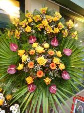 Wieniec z żywych kwiatów, wielkość: duży, storczyki złote (Cymbidium), róże herbaciane, anthurium bordowe, gerbery złote, liść palmy, podkład jodłowy, zieleń dekoracyjna.