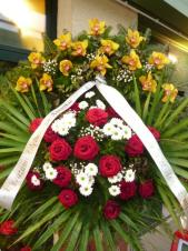Wieniec z żywych kwiatów, wielkość: średni, storczyki złote (Cymbidium), róże czerwone, chryzantemy białe, liść palmy, podkład jodłowy, szarfa plastikowa, druk komputerowy.