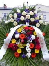 Wieniec z żywych kwiatów, wielkość: średni, róże białe, irysy fioletowe,  storczyki żółte (Cymbidium), chryzantemy zielone i kremowe, gerbery złote, goździki gałązkowe, liść palmy, podkład jodłowy, szarfa plastikowa, druk komputerowy.