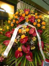 Wieniec z żywych kwiatów, wielkość: bardzo duży, storczyki złote (Cymbidium), róże herbaciane, anthurium bordowe, liść palmy, podkład jodłowy, zieleń dekoracyjna, szarfa plastikowa, nadruk złoty.