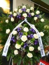 Wieniec z żywych kwiatów, wielkość: średni, róże białe, irysy fioletowe, liść palmy, podkład jodłowy, szarfa satynowa nadruk czarny, druk komputerowy (+20zł).