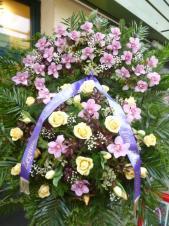 Wieniec z żywych kwiatów, wielkość: duży, storczyki różowe (Cymbidium), róże ecru, tulipany kremowe, liść chico i fenix, podkład jodłowy, szarfa satynowa nadruk złoty szer. 7cm, kolor wstęgi fioletowy, druk komputerowy (+30zł).