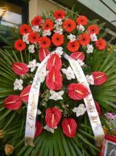 Wieniec z żywych kwiatów, wielkość: duży, gerbery czerwone,  storczyki białe (Cymbidium), anthurium czerwone, liść palmy, podkład jodłowy, szarfa satynowa, druk komputerowy (+20zł).