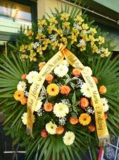 Wieniec z żywych kwiatów, wielkość: bardzo duży, róże herbaciane,  storczyki żółte (Cymbidium), gerbery kremowe i żółte, liść palmy, podkład jodłowy, szarfa satynowa 10cm. szer. w kolorze złotym, druk komputerowy (+40zł).