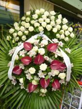 Wieniec z żywych kwiatów, wielkość: bardzo duży, róże białe,  storczyki białe (Cymbidium), anthurium bordowe, liść palmy, podkład jodłowy, szarfa satynowa 10cm. szer., druk komputerowy (+30zł).