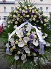 Wieniec z żywych kwiatów, wielkość: bardzo duży, róże białe,  storczyki białe (Cymbidium), anthurium białe, eustomy fioletowe, liść palmy, podkład jodłowy, szarfa satynowa 10cm. szer., druk komputerowy (+30zł).
