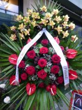 Wieniec pogrzebowy z żywych kwiatów, wielkość: duży, storczyki żółte, róże pąsowe, anthurium czerwone, liść palmy, podkład jodłowy, zieleń dekoracyjna, szarfa satynowa biała 7 cm. (+20zł)