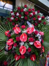 Wieniec pogrzebowy z żywych kwiatów, wielkość: duży, róże pąsowe, anthurium czerwone, liść palmy, podkład jodłowy, zieleń dekoracyjna, szarfa czarna satynowa 7 cm. (+30zł)