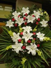 Wieniec z żywych kwiatów, lilia biała, róża różowa, chryzantema zielona (Santini), mieczyk zielony, podkład jodłowy, zieleń dekoracyjna, liść plamy.