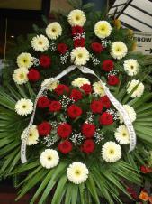 Wieniec z żywych kwiatów, gerbera kremowa, róża pąsowa, podkład jodłowy, zieleń dekoracyjna, liść plamy.