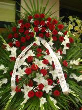 Wieniec z żywych kwiatów, lilia biała, róża pąsowa, mieczyk biały, podkład jodłowy, zieleń dekoracyjna, liść plamy.