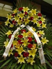 Wieniec z żywych kwiatów, lilia kremowa, róża czerwona, storczyk złoty (Cymbidium), chryzantema zielona (Santini), podkład jodłowy, zieleń dekoracyjna, liść plamy.