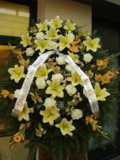 Wieniec z żywych kwiatów, lilia kremowa, róża kremowa, mieczyk herbaciany, storczyk zielony (Cymbidium), podkład jodłowy, zieleń dekoracyjna.