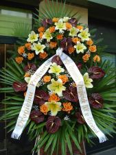 Wieniec pogrzebowy z żywych kwiatów, wielkość: bardzo duży, anthurium brązowe (Choco), róże herbaciana (Finnes), lilie kremowe (Conca D'or), liście palmy, podkład jodłowy, zieleń dekoracyjna, szarfa satynowa 10cm, druk komputerowy.
